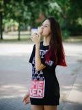 El encantar, muchacha del inconformista de la moda en verano viste la consumición del helado en un fondo urbano Concepto urbano d Fotografía de archivo