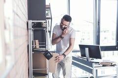 El encargado adulto de moda está trabajando mientras que habla en el teléfono móvil Fotografía de archivo