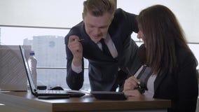 El encargado creativo y la empresaria se divierten que charlan en oficina usando el ordenador almacen de metraje de vídeo