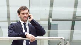 El encargado de aspiración joven tiene un tiempo que negocia en un smartphone en pasillo moderno de la oficina almacen de video