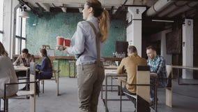 El encargado de sexo femenino moreno viene a la oficina moderna en el trabajo La mujer joven saluda con los colegas, trae el café almacen de video