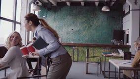 El encargado de sexo femenino moreno viene a la oficina moderna en el trabajo La mujer joven saluda con los colegas, trae el café almacen de metraje de vídeo
