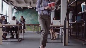 El encargado de sexo femenino moreno viene a la oficina moderna La mujer joven saluda con los colegas, trae el café al amigo MES  metrajes