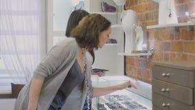 El encargado de ventas demuestra yewellery al comprador femenino en joyería almacen de metraje de vídeo