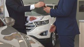 El encargado de ventas vende el coche al cliente en la representación almacen de metraje de vídeo