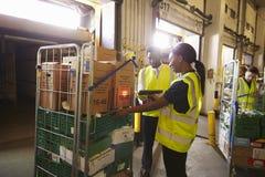 El encargado de Warehouse supervisa a una mujer que prepara una entrega fotos de archivo libres de regalías