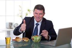 El encargado en la oficina come la ensalada verde fotos de archivo