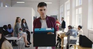 El encargado europeo hermoso de sexo masculino joven triste es encendido y de abandono de trabajo en la oficina multiétnica, yénd almacen de video