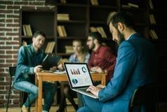 El encargado Finance trabaja con los gráficos del márketing en el ordenador portátil Fotografía de archivo libre de regalías