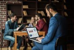 El encargado Finance trabaja con los gráficos del márketing en el ordenador portátil Imagenes de archivo