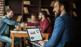 El encargado Finance trabaja con los gráficos del márketing en el ordenador portátil Imagen de archivo