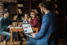 El encargado Finance trabaja con los gráficos del márketing en el ordenador portátil Foto de archivo libre de regalías