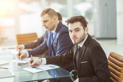 El encargado Finance y el equipo del negocio están trabajando con las cartas financieras en su escritorio Fotografía de archivo