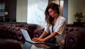 El encargado hermoso del empleado de oficina de la mujer de la chica joven se sienta en una tabla con un ordenador portátil Inter imágenes de archivo libres de regalías