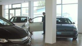 El encargado invita a una empresaria que examine el automóvil en la concesión de coche almacen de metraje de vídeo