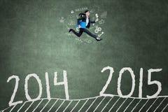 El encargado joven salta sobre el número 2014 a 2015 Imagen de archivo libre de regalías