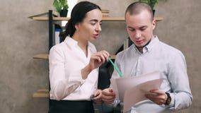 El encargado mira documentos del empleado menor en oficina
