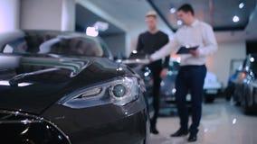 El encargado muestra a cliente el coche eléctrico metrajes