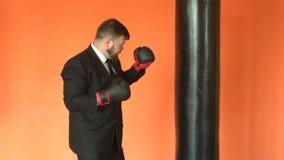 El encargado o el jefe en guantes de boxeo bate el saco de arena en gimnasio El hombre de negocios en traje negro alivia la tensi almacen de video