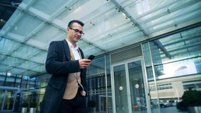 El encargado sonriente está caminando al lado de un centro de la oficina con un smartphone Tiro épico rojo de la cámara del cine