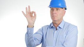 El encargado Wearing Engineer Helmet hace buena muestra del trabajo gestos de mano ACEPTABLES foto de archivo libre de regalías