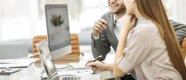 El encargado y el contable son que sientan y de discusiones de cartas financieras con los beneficios de la compañía en el lugar d imagen de archivo