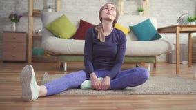El enfermo de cáncer de la mujer joven después de la quimioterapia en una bufanda en la cabeza hace estirar antes de entrenar en  metrajes