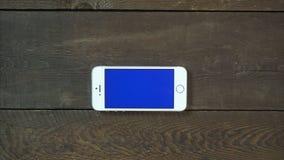 El enfoque hacia fuera da Smartphone con la pantalla azul Fotografía de archivo