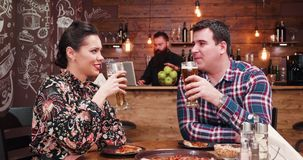 El enfoque hacia fuera tiró de la cerveza de consumición de los pares caucásicos y pizza de la consumición en pub o restaurante r almacen de metraje de vídeo