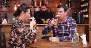 El enfoque hacia fuera tiró de la cerveza de consumición de los pares felices del inlove en restaurante elegante del pub del vint metrajes