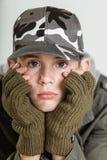 El enfurruñarse adolescente masculino mientras que sostiene la cara en guantes Imagen de archivo