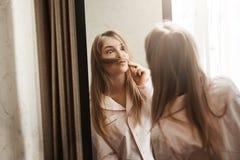El engañar alrededor mientras que nadie ve Retrato de la mujer rubia juguetona adorable que hace el bigote de filamento del pelo, Imagen de archivo