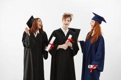 El engañar de discurso sonriente de tres graduados alegres sosteniendo los diplomas sobre el fondo blanco Imagen de archivo libre de regalías