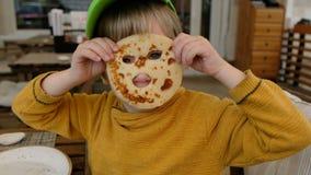 El engañar divertido del muchacho, haciendo una máscara de la crepe en un restaurante almacen de video