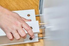 El ensamblador de los muebles hace servicio profesional del montaje del paquete plano fotos de archivo