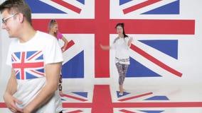 El ensayo de dos mujeres baila a los ejecutantes que se colocan en fondo de la bandera británica metrajes
