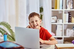El enseñar casero, búsqueda y estudio, nuevo conocimiento niño feliz en la tabla con el ordenador estudiante del niño pequeño que imágenes de archivo libres de regalías