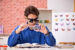 El entomólogo del estudiante que estudia la nueva especie de mariposas fotos de archivo