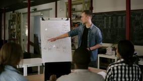 El entrenador joven caucásico da la presentación para los empresarios que trabajan con el flipchart, equipo multirracial diverso  almacen de metraje de vídeo