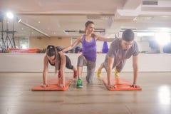 El entrenamiento de instructor de la aptitud empuja hacia arriba el gimnasio de las personas del grupo tres Fotografía de archivo libre de regalías
