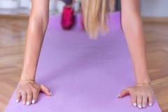 El entrenamiento de la mujer de la aptitud del deporte empuja para arriba hacia adentro casa en la estera púrpura de la yoga fotografía de archivo