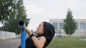 El entrenamiento de la mujer de la aptitud intenta hacer ejercicios en una barra horizontal al aire libre metrajes