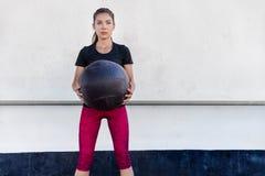 El entrenamiento de la mujer del gimnasio de la aptitud arma con la bola de medicina Foto de archivo