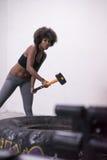 El entrenamiento de la mujer negra con el martillo y el tractor cansan Fotografía de archivo