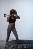 El entrenamiento de la mujer negra con el martillo y el tractor cansan Imagen de archivo