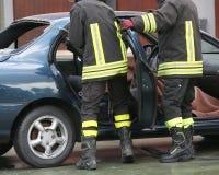 El entrenamiento del bombero a extraer atrapó al hombre en el coche Fotografía de archivo