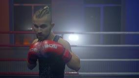 El entrenamiento del boxeo, varón del luchador en guantes realiza sacadores de la caja en el anillo durante deportes que entrena  almacen de metraje de vídeo