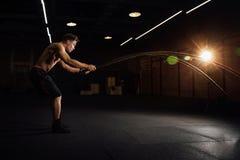 El entrenamiento del hombre de la aptitud con batalla ropes en el gimnasio cuerpo cabido ejercicio de formación en club torso imagen de archivo