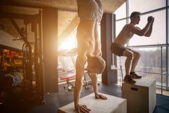 El entrenamiento del hombre del pectoral de la posición del pino en el pus del gimnasio sube Foto de archivo