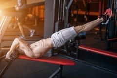 El entrenamiento del hombre del pectoral de la posición del pino en el pus del gimnasio sube Imagen de archivo libre de regalías